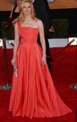 Michael Kors' one-shoulder gown in orange red on red carpet.PNG